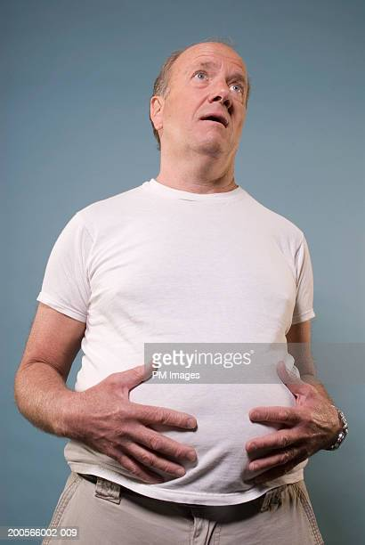 Middle aged man with hands on stomach, upper half, low angle view