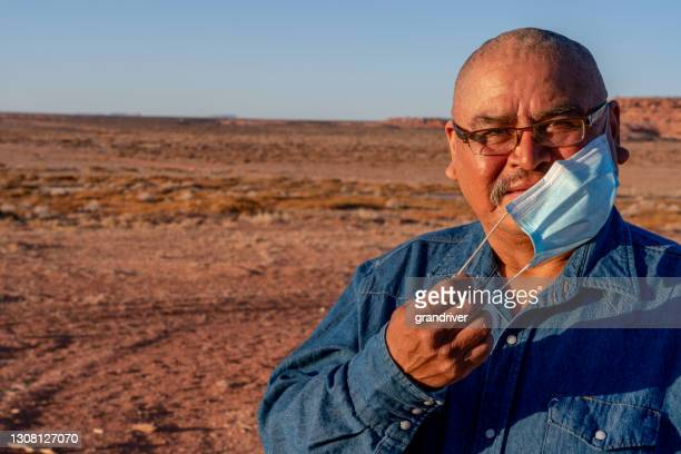 middle aged navajo man on his rural property in monument valley utah near arizona, removing his mask, during the covid-19 corona virus pandemic - cherokee culture stock pictures, royalty-free photos & images