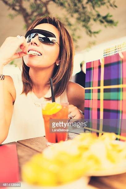 Middle aged real woman  in sidewalk cafe with shopping bags