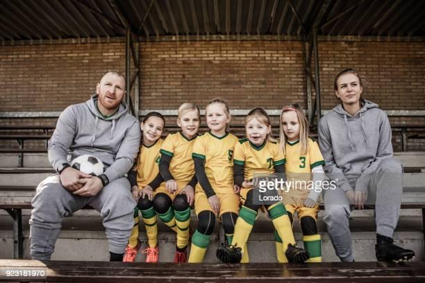 milieu âgés redhead père et fille blonde, entraîneur de football pour une équipe de football de la jeune fille - groupe moyen de personnes photos et images de collection