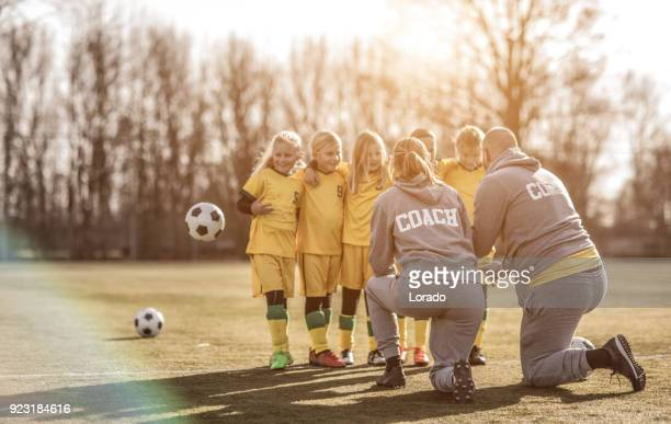 Middle Aged Redhead Father and blonde daughter coaching soccer together to a Girl Football team
