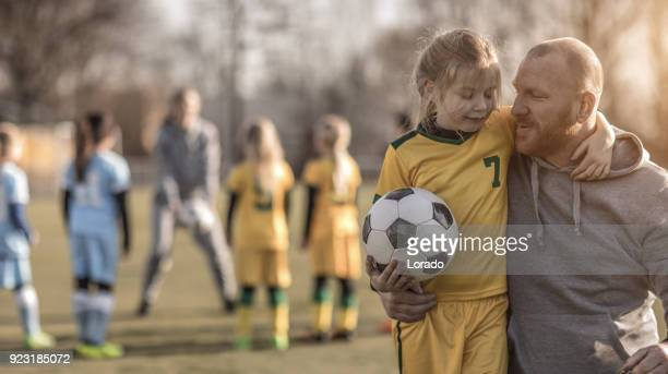 middle aged redhead father and blonde daughter coaching soccer together to a girl football team - practicing stock pictures, royalty-free photos & images