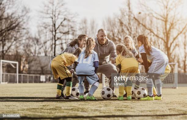 middle aged redhead father and blonde daughter coaching soccer together to a girl football team - gruppo medio di persone foto e immagini stock