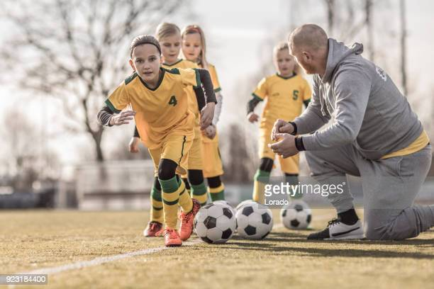 Middle Aged Redhead Father coaching soccer to a Girl Football team at training