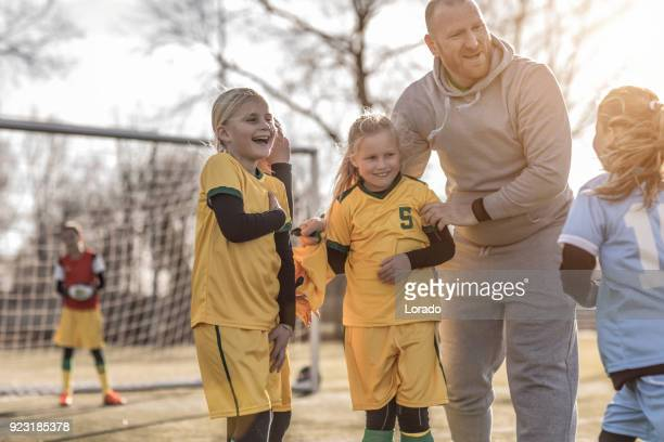 middle aged redhead father coaching soccer to a girl football team at training - coach stock pictures, royalty-free photos & images