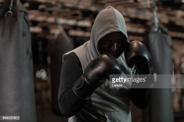 middle aged redhead handsome boxer fighter training with heavy bag in gym setting - mixed martial arts stock pictures, royalty-free photos & images