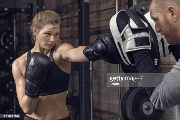 middle aged redhead handsome personal trainer and beautiful young female athlete in gym setting - mixed martial arts stock pictures, royalty-free photos & images