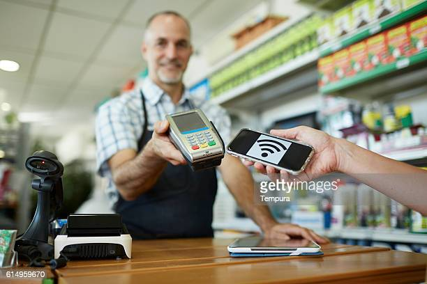 Middle aged sales clerk using using contactless payment