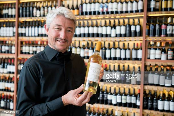 Middle aged salesman at a wine store holding a white wine bottle looking at camera smiling
