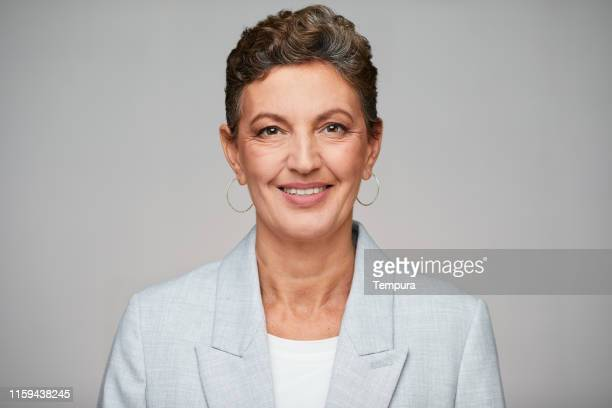 middle aged sophisticated businesswoman studio headshot, wearing a suit. - grey suit stock pictures, royalty-free photos & images