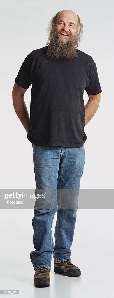 middle aged thin balding caucasian adult male with a gray beard wearing jeans and a dark t-shirt stands with hands behind back looking at the camera with a questioning expression : Stock Photo