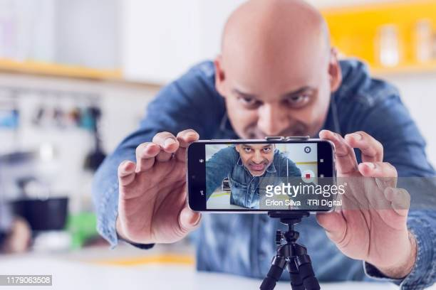 middle aged vlogger man preparing himself to record diy content for his blog - filming stock pictures, royalty-free photos & images