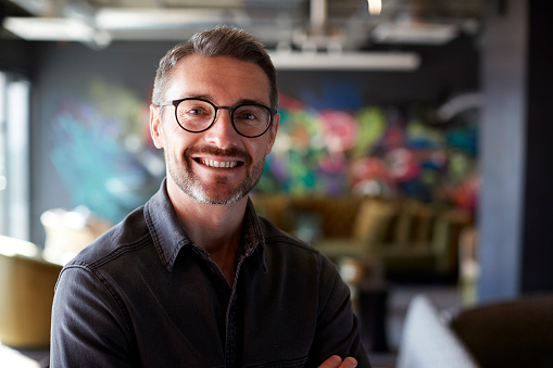 Middle aged white male creative in casual office lounge area looks to camera smiling, close up 1146478798