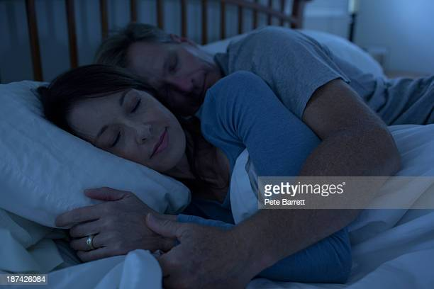 Middle aged woman and man sleeping in bed