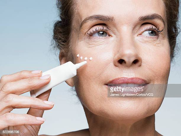Middle aged woman applying cream on face, Studio shot