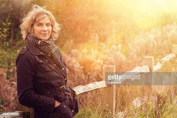Meio envelhecido mulher na fazenda muro