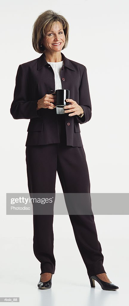 middle aged woman dark hair wears dark business suit stands looking to the camera coffee cup in hand : Foto de stock