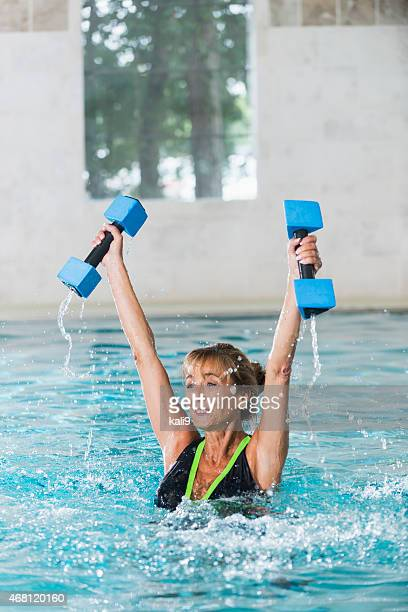 Middle aged woman doing water aerobics with dumbbells