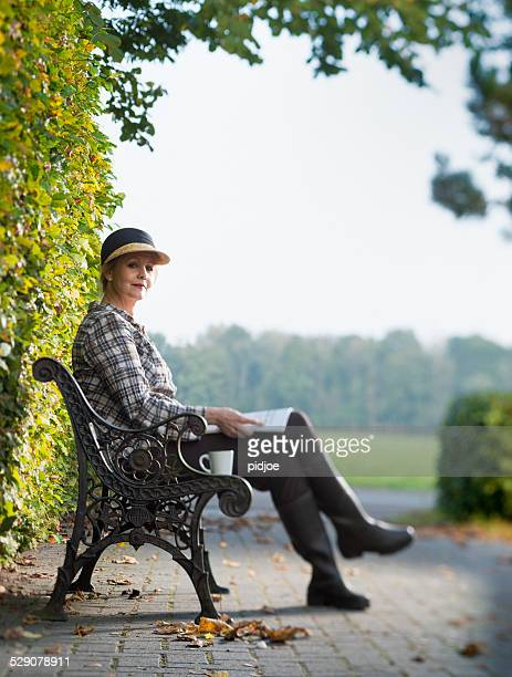 middle aged woman enjoying the autumn sun.