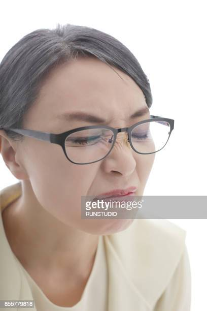 middle aged woman frowning nose with glasses - ugly asian woman stock photos and pictures