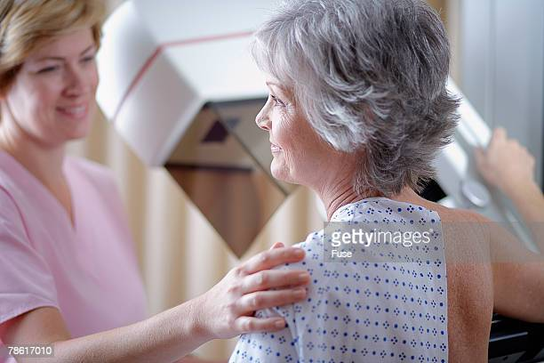 middle aged woman getting mammogram - mammogram stock pictures, royalty-free photos & images