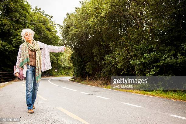 middle aged woman hitchhiking