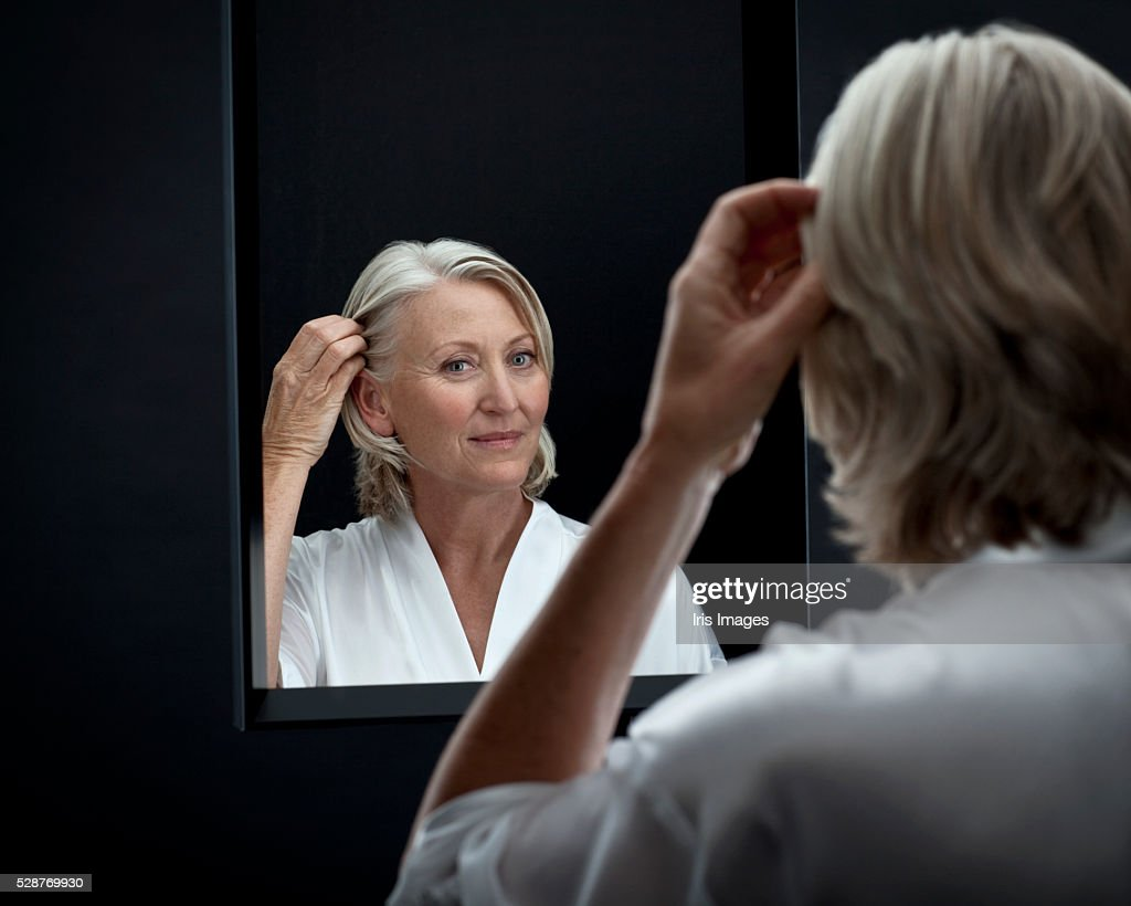 middle aged woman looking in a mirror stock photo getty