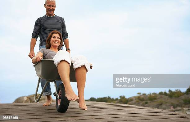 Middle aged woman pushed in wheel barrow
