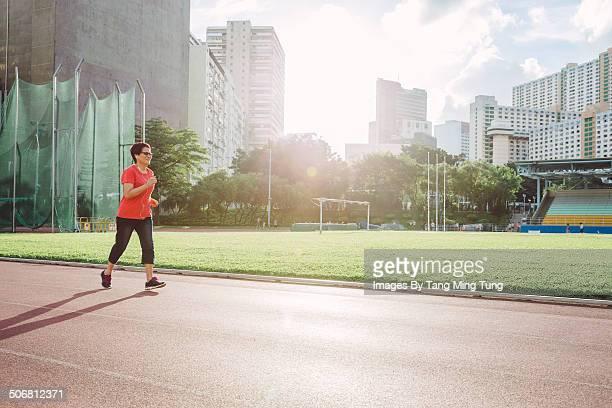 Middle aged woman running on track joyfully