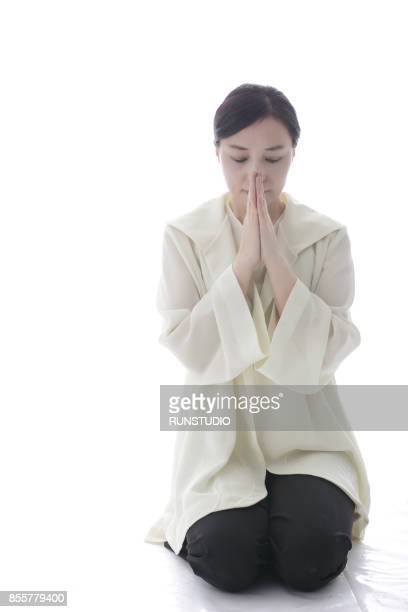 middle aged woman sitting on her feet knees together and praying - mulher orando de joelhos imagens e fotografias de stock