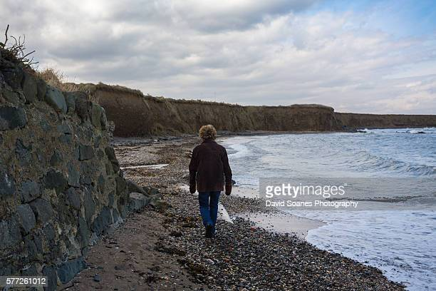 a middle aged woman standing on a beach in balbriggan, dublin, ireland - david cliff stock pictures, royalty-free photos & images