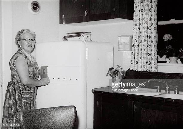Middle aged woman stands by her refrigerator, ca. 1955