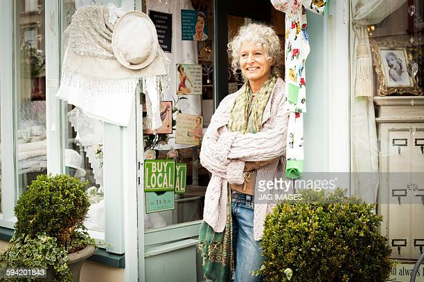 Middle aged woman stands in doorway of shop