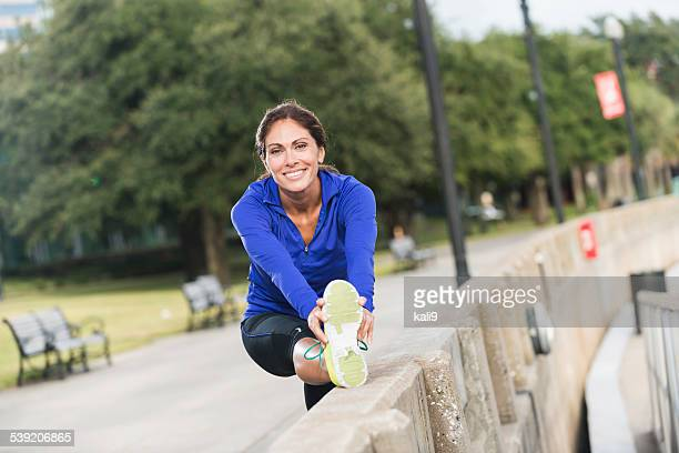 Middle aged woman stretching after a jog in the park