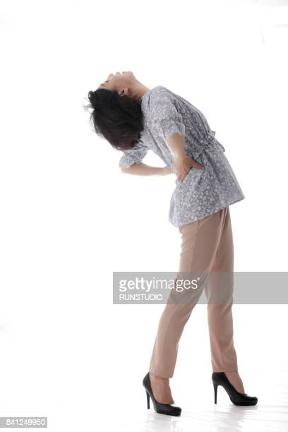 middle aged woman suffering from backache - bending over backwards stock photos and pictures