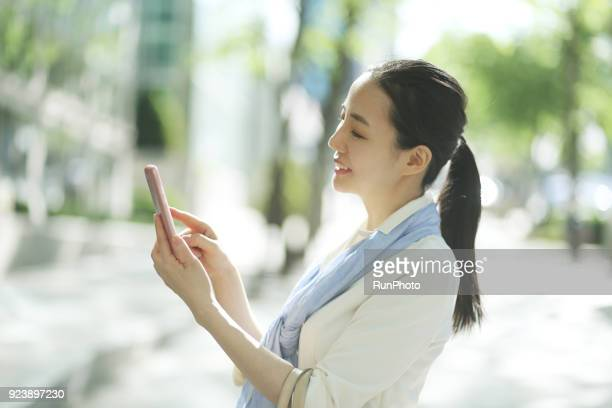 middle aged woman texting message with smartphone in city street - 可動性 ストックフォトと画像