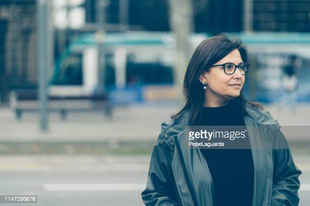 middle aged woman walking in barcelona - desaturated stock pictures, royalty-free photos & images