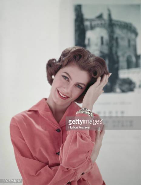 A middle aged woman wearing pink corduroy longsleeved shirt circa 1955