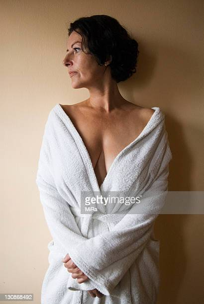 middle aged woman wears white bathrobe that is pulled open over her cleavage - escote fotografías e imágenes de stock