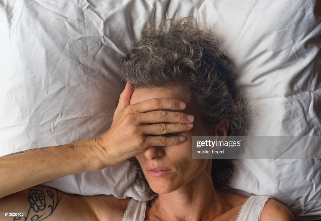 Middle aged woman with hand over eyes on pillow from abvove : Stock Photo