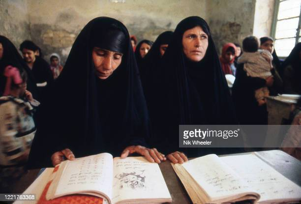 Middle aged women dressed in traditional chadors sit at desk in classroom while studying reading and writing circa 1978;