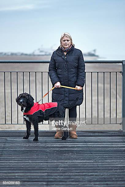 Middle aged women with her dog on a pier