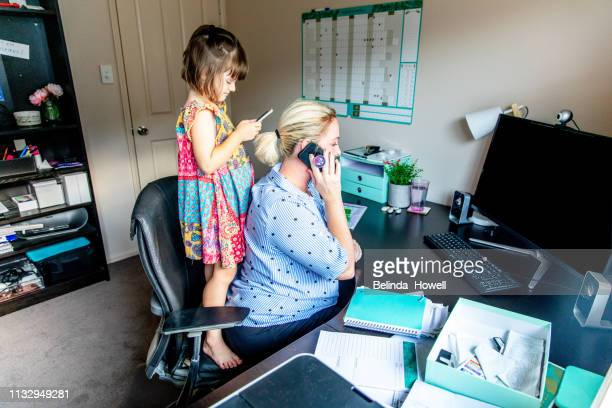 middle aged women working from home in office whilst also looking after her young daugther. - working mother stock pictures, royalty-free photos & images