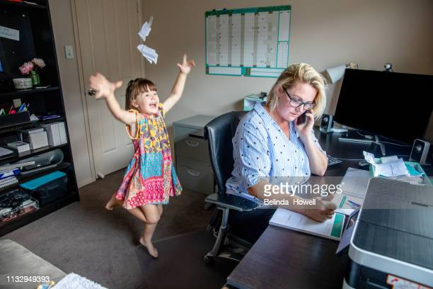 middle aged women working from home in office whilst also looking after her young daugther. - quedarse en casa frase fotografías e imágenes de stock