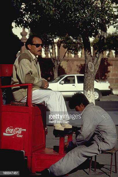 CONTENT] A middle class man with flashy sunglasses gets his shoes polished on a chair with a Coca Cola sign
