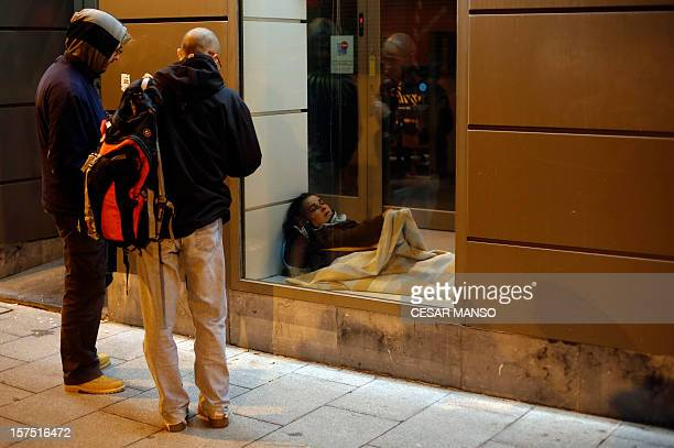 "Middle class to underclass in impoverished Spain"" Caritas volunteers look at a homeless woman sleeping on the entrance of a bank office before asking..."