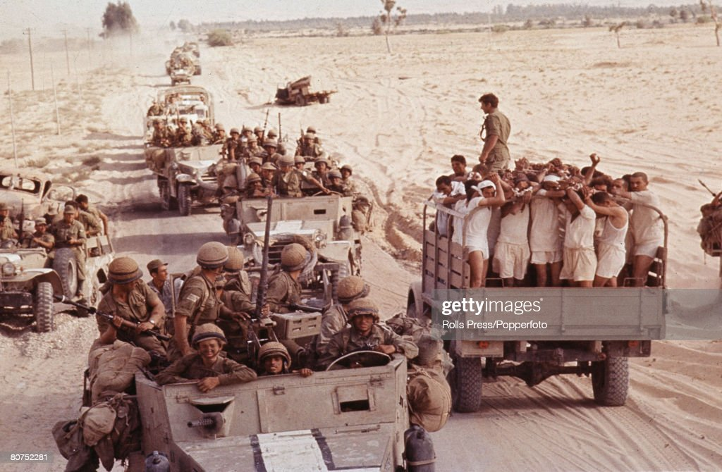 Middle East 8th June 1967. Six Day War. Sinai Desert. Captured Egyptian soldiers are transported in an open top truck to a prisoner of war camp (POW) as an Israeli armoured convoy moves through the desert after capturing El Arish. : News Photo