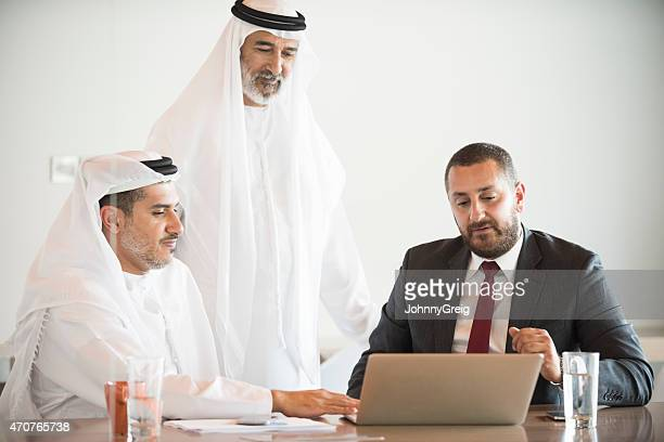 Middle East businessmen using laptop at conference table in office