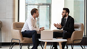 Middle eastern and caucasian ethnicity businessmen talking negotiating indoors