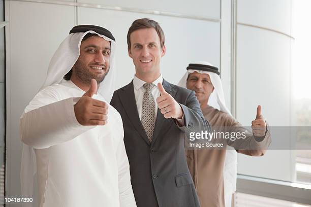 Middle eastern and western businessmen giving thumbs up